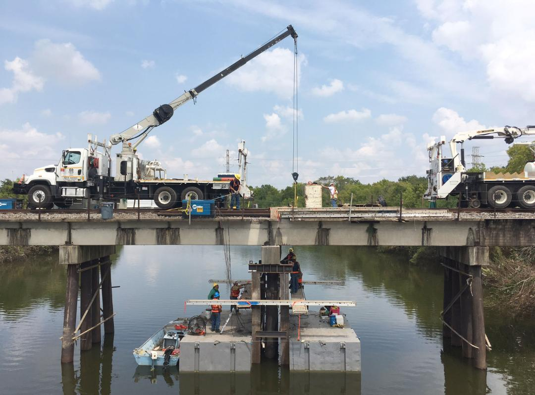 Bridge employees use a truck crane to repair a pier in Houston, Texas.