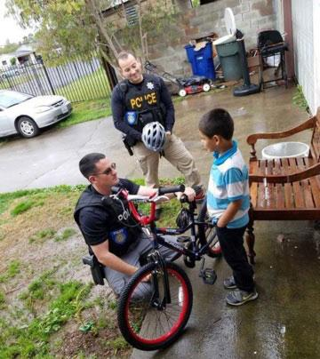 Sacramento police offcers discuss safety and build relationships through the bike giveaway program.