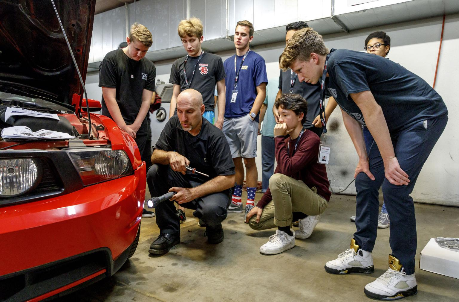 Teen Auto Workshop participants gather around to watch an in-progress repair.