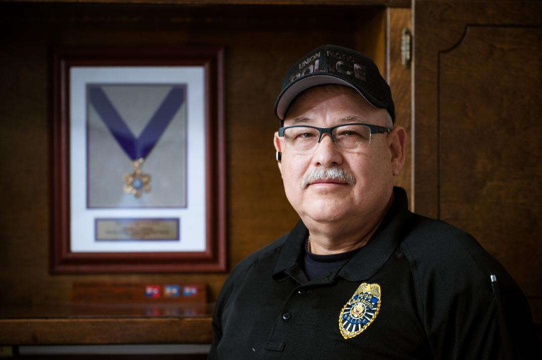 Oscar Garcia, Jr., stands in front of his purple heart medal.