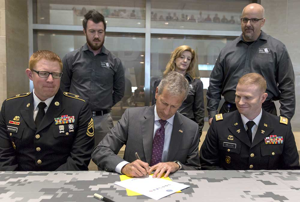Building America Report 2016 - Lance Fritz signs the Employer Support of the Guard and Reserve documents.